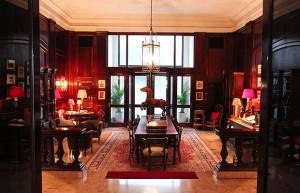 Do hall do hotel, esta é a visão que se tem da entrada da biblioteca. Os tons quentes e a madeira deixam o local especialmente acolhedor e confortável (Foto: Divulgação)