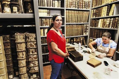 Numa sala escondida de um dos pisos inferiores, fica uma das oficinas de trabalho de Elsa Girão (de frente), a técnica de restauro da Biblioteca Fotografia © Fernando Fontes / Global Imagens