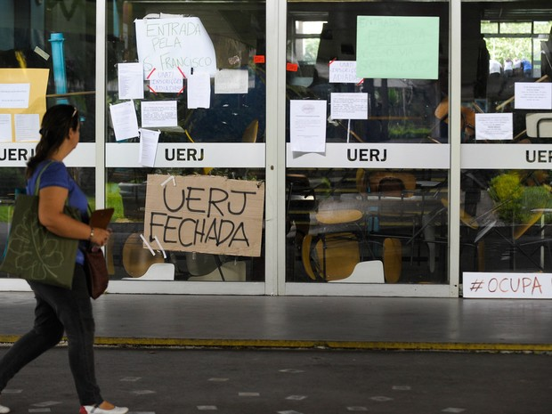 Uma mulher passa por um prédio da Universidade Estadual do Rio de Janeiro durante ocupação de estudantes em 2015. (Foto: Tânia Rego/Agência Brasil)